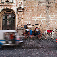Traffic passes as horse-drawn carriages wait outside of the ruins of la Iglesia y Convento de Santa Clara at the east end of el Parque de la Unión, Antigua, Guatemala.