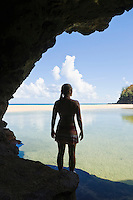 A woman standing at the entrance to a cave looking out over a pool of water to a beach and a ocean beyond.  Hanakapiai Beach, Na Pali Coast of Kauai, Hawaii