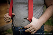 Farming in Oregon and Washington.  A farmer in red suspenders with scratched up hands.