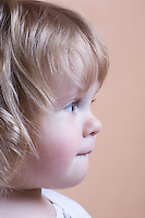 Side view profile of blonde toddler with baby curls