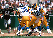 St. Louis Rams quarterback Chris Miller (12) hands off the ball to Rams running back Jerome Bettis (36) while Oakland Raiders linebacker Mike Morton (50) closes in for a tackle attempt during the 1995 NFL preseason football game against the Oakland Raiders on Aug. 12, 1995 in Oakland. The Raiders won the game 27-22. (©Paul Anthony Spinelli)