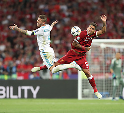 May 26, 2018 - Kiev, Ukraine - Liverpool's Brazilian forward Roberto Firmino (R) jumps for the ball with Real Madrid's Spanish defender Sergio Ramos (L) during the UEFA Champions League final football match between Liverpool and Real Madrid at the Olympic Stadium in Kiev, Ukraine, on May 26, 2018. (Credit Image: © Raddad Jebarah/NurPhoto via ZUMA Press)