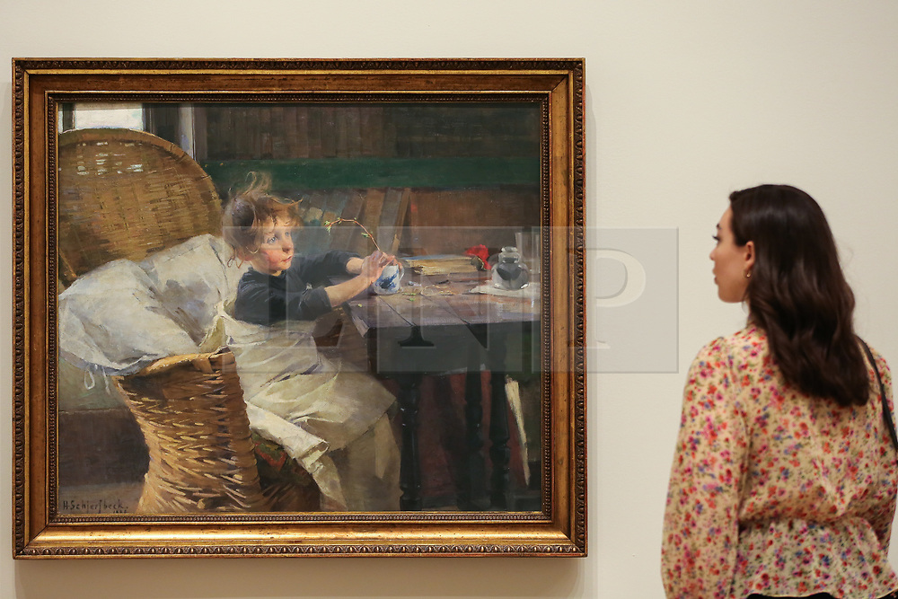 """© Licensed to London News Pictures. 17/07/2019. London, UK. A staff member views Helene Schjerfbeck's painting """"The Convalescent (1888)"""" at Royal Academy of Arts during the preview of her first ever exhibition in the UK. The exhibition features around 65 portraits, landscapes and still life, charting the development of Helene Schjerfbeck's work from a naturalistic style inspired by French Salon painters in the early 1880s, to a radically abstracted and modern approach from the turn of the twentieth century onwards. The exhibition runs  from 20 July to 27 October 2019. Photo credit: Dinendra Haria/LNP"""