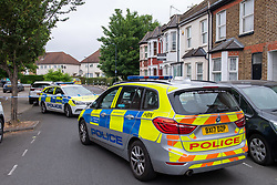 © Licensed to London News Pictures. 04/06/2020. London, UK. Police vehicles sit on Bridge Road at the corner of Energen Close. An investigation has been launched after three adults and a child were shot in Brent. Police were called at 21:45 BST on Wednesday 03/06/2020 to reports of shots fired in Energen Close, Harlesden. Metropolitan Police Service officers attended along with London Ambulance Service and found four people suffering gunshot injuries. All four were taken to hospital. Photo credit: Peter Manning/LNP