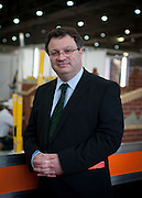 .Dr. Stephen Farry Employment and Learning Minister for Northern Ireland visits the ExCel Centre and poses for a portrait in front of the bricklaying stand in London on October 8th 2011.