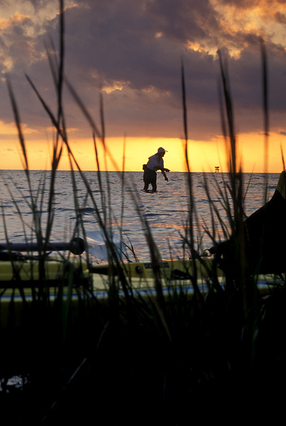 Stock photo of a fisherman with his kayak flyfishing in Galveston Bay fishing at dusk