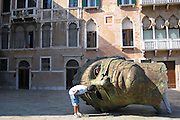 Tourists investigate a head sculpture in Venice, Italy