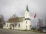 Flagget til topps utenfor Selbustrand kapell, Selbu i Sør-Trøndelag. Selbustrand kirke ligger i Selbu sokn i Stjørdal prosti. Den er bygget i tre og ble oppført i 1901. Kirken har langplan og 300 sitteplasser.<br /> Arkitekt er O.Alfstad. Det var to kirker i Neadalsføret, Selbu og Tydal, da det ved kgl.res. 20.10.1898 ble det tillatt å bygge kapell på Leikvoll for Selbustranda. I Selbustrand kapell skulle det holdes 12 gudstjenester årlig.