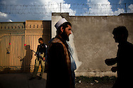 Locals walk past a Pakistani policeman guarding an entrance to the compound where Osama Bin Laden was killed in an operation by US Navy Seals, on May 4, 2011, in Abottabad, Pakistan.  The operation, code-named Operation Neptune Spear, was launched from neighbouring Afghanistan by Seal Team Six. U.S. forces took bin Laden's body to Afghanistan for identification, then dumped it the Arabian Sea. Pakistan has since been widely suspected as having prior knowledge of his whereabouts as the compound was less than a kilometre from the country's biggest military academy. Osama bin Laden was allegedly responsible for supporting the bombing of the US Embassy in Nairobi, Kenya, the attack on the USS Cole and the suicidal attacks of September 11, 2001 in the US. (Photo by Warrick Page)