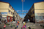 Manenberg, South Africa &ndash; Gang warfare raged for weeks in this township, with dozens of shootings and 10 murders as two gangs fought for control. Sixteen schools in the battle zone were closed, and some called for the Army to<br /> come in. High levels of violence persist in South Africa, particularly in the townships,<br /> where joblessness is high. Manenberg, notoriously violent, is just 15 minutes from<br /> the beautiful seaside enclaves of Cape Town. Religious leaders helped broker a truce<br /> between the two main gangs. Peace is holding, for the most part, but there&rsquo;s still a<br /> lack of jobs and an abundance of &ldquo;Tik,&rdquo; a nasty form of cheap methamphetamine.<br /> Community leaders are optimistic, though: Programs and interventions are being organized, and the police will maintain a strong presence here for the rest of the year.<br /> <br /> Children play in a housing courtyard in the middle of the day on September 11, 2013 in Manenberg, a township of Cape Town, South Africa. Photo by Ann Hermes/The Christian Science Monitor