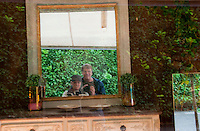 The photographer and traveling companion reflected in a mirror inside a shop window in France.