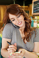 Beautiful woman writing on paper while listening to mobile phone in supermarket