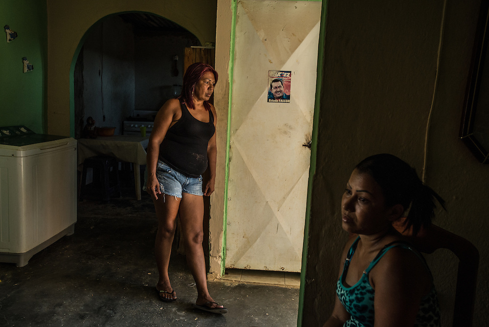 """LA VELA, VENEZUELA - SEPTEMBER 10, 2016: Maria Piñero (left) and her daughter, Roymar Bello at their home in La Vela.  Ms. Bello had a traumatic experience being smuggled to Curacao island to work undocumented.  Smugglers threw her into the water, even though she could not swim, and other migrants had to drag her to shore by her hair. Her mother Maria had given her Roymar a life vest just before she left, knowing that she could not swim. But the smuggler ripped it off her daughter just before throwing her into the sea, claiming that the swells were so high she was better off swimming under the waves. Now, despite Ms. Bello's ordeal, Maria vowed to make the journey by boat, too. """"I'm nervous,"""" she began. """"I'm leaving with nothing. But I have to do this. Otherwise, we will just die here hungry."""" PHOTO: Meridith Kohut for The New York Times"""