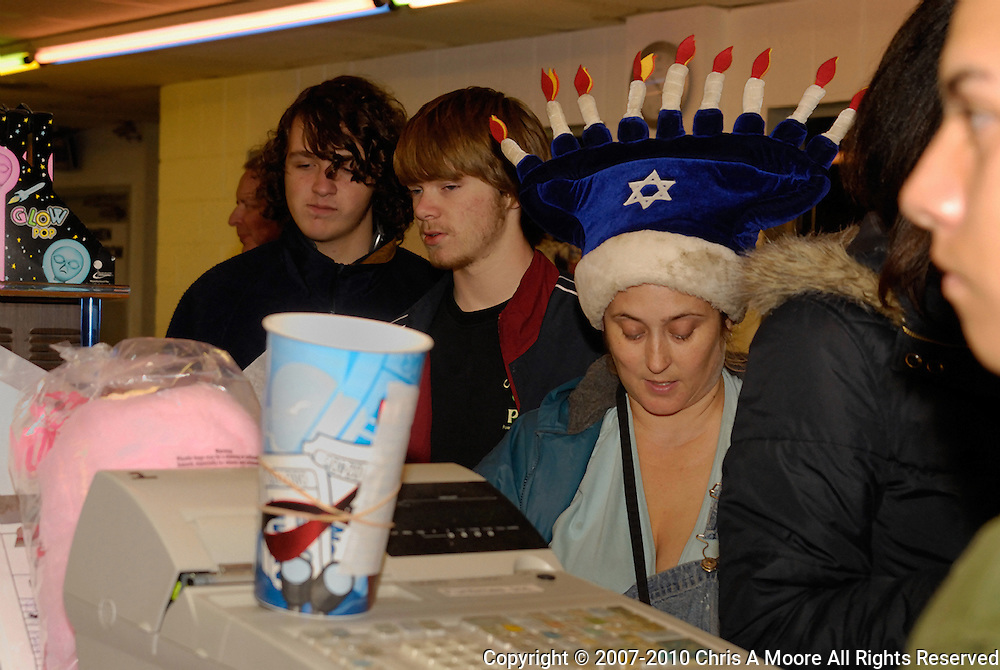 People dress up for the closing of the Cinderella Twin Drive-in, south Denver. Here a woman wears a Menora hat while she pays at the snack bar.