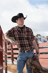 sexy cowboy leaning on a fence on a ranch in New Mexico