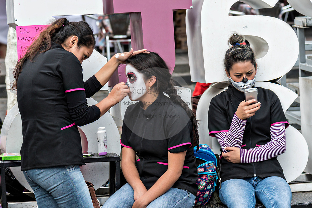 Mexican women have face paint applied during the Day of the Dead or Día de Muertos festival October 31, 2017 in Patzcuaro, Michoacan, Mexico. The festival has been celebrated since the Aztec empire celebrates ancestors and deceased loved ones.