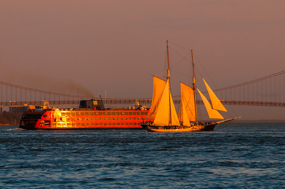 Sailboats and sailing ship with Staten Island Ferry passing behind in New York Harbor at sunset (Verrazano-Narrows Bridge in background), New York, New York USA.