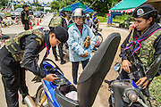 "25 OCTOBER 2012 - TAK BAI, NARATHIWAT, THAILAND: Thai women Rangers (paramilitary operating under Army command) check a woman's motorcycle at a checkpoint in Tak Bai, Thailand. The ""Tak Bai Incident"" took place on Oct. 25 in Tak Bai, Narathiwat, Thailand during the Muslim insurgency in southern Thailand. On that day, a crowd gathered to protest the arrest of local residents. Police made hundreds of arrests during the protest and transported the arrested to Pattani, about two hours away, in another province. They were transported in locked trucks and more than 80 people suffocated en route. This enraged local Muslims and shocked people across Thailand. No one in the Thai army accepted responsibility for the deaths and no one was ever charged. In the past, the anniversary of the incident was marked by protests and bombings. This year it was quiet. More than 5,000 people have been killed and over 9,000 hurt in more than 11,000 incidents, or about 3.5 a day, in Thailand's three southernmost provinces and four districts of Songkhla since the insurgent violence erupted in January 2004, according to Deep South Watch, an independent research organization that monitors violence in Thailand's deep south region that borders Malaysia.   PHOTO BY JACK KURTZ"