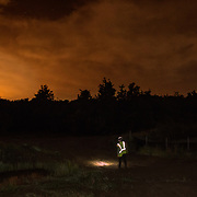STERLING, VA - JUN13: Bethany Gregory, a field technician with GAI Consultants, walks into the woods with a headlamp to check mist nets for bats, July 13, 2015, during a bat census to make sure the planned Silver Line train yard near Dulles Airport doesn't impact the bats living in the woods near the site. Fine 'mist nets' are hung from polls to capture bats and determine whether there is a threatened bat species in the area. The bats are then released. (Photo by Evelyn Hockstein/For The Washington Post)