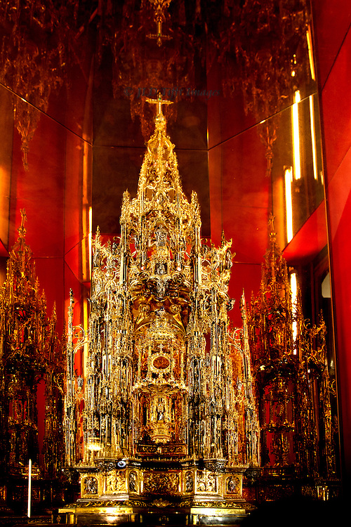 Elaborate gilded monstrance on display in the Cathedral of Toledo.  It sits in a dedicated niche with red walls.