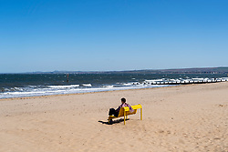 Portobello beach and promenade near Edinburgh during Coronavirus lockdown on 19 April 2020. Woman sits alone on yellow bench on the empty  beach.