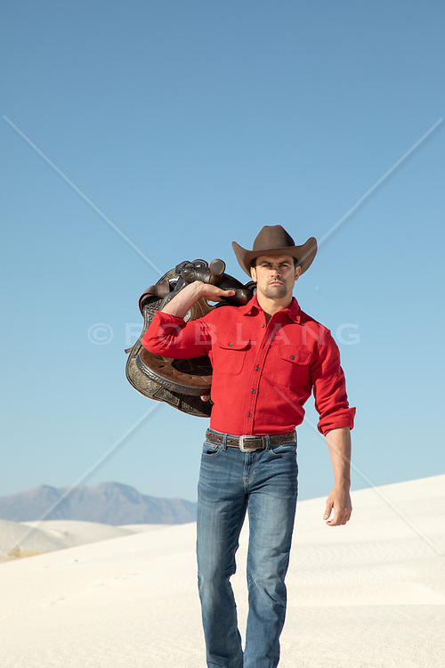 All American cowboy holding a saddle