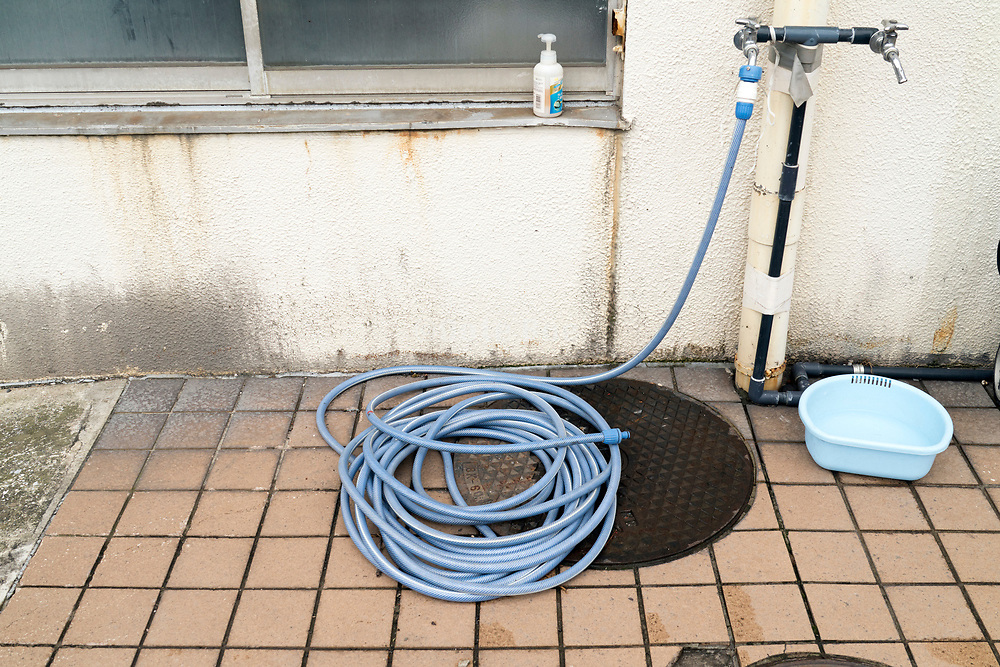 rolled up water hose at an outdoors faucet