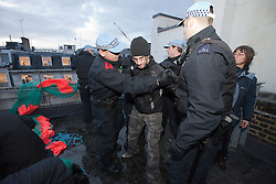 "© Licensed to London News Pictures. 30/11/2011. London, UK. ""Occupy"" protesters get on to the roof of Panton House in Haymarket. They hung a banner from the roof before police came up and arrented several for Criminal Trespass. Photo credit : Joel Goodman/LNP"