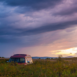 An abandoned van in a field under a summer storm at sunset in Mars Hill, Maine.
