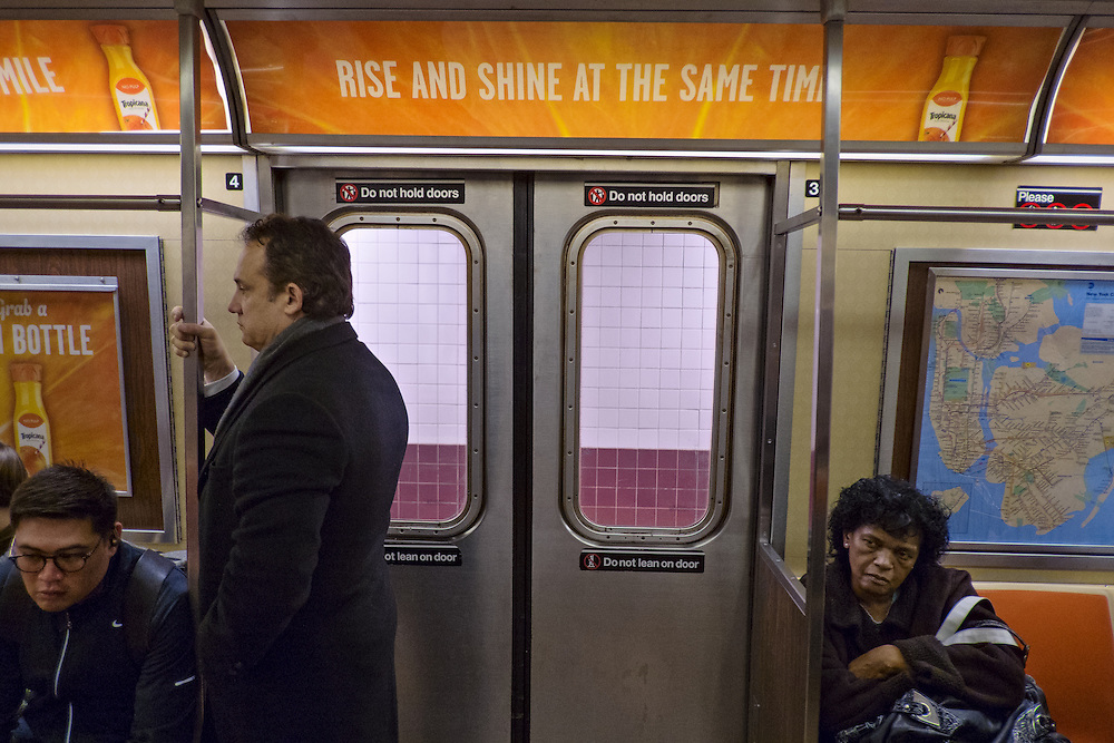 "Subway riders beneath advertisement reading, ""Rise and shine at the same time"", New York, NY, US"