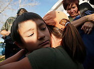 Mayumi Heene (upper R), mother of six-year-old Falcon Heene (L), is hugged by a neighbor as Falcon is hugged by another neighbor outside their house in Fort Collins, Colorado October 15, 2009. Falcon, who set off a massive search and rescue operation and media frenzy after it was reported he was inside a homemade helium balloon that broke loose and drifted for hours thousands of feet above Colorado has been found safe in his attic, police said on Thursday.  REUTERS/Rick Wilking (UNITED STATES SOCIETY IMAGES OF THE DAY)