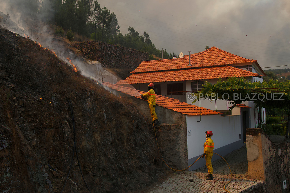 LEIRIA, PORTUGAL - JUNE 20:  A firefighter extingish flames approaching to Mega Fundeira village after a wildfire took dozens of lives on June 20, 2017 near Picha, in Leiria district, Portugal. On Saturday night, a forest fire became uncontrollable in the Leiria district, killing at least 62 people and leaving many injured. Some of the victims died inside their cars as they tried to flee the area.  (Photo by Pablo Blazquez Dominguez/Getty Images)