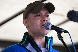 London, UK. 1st December, 2018. Clive Lewis MP, Shadow Treasury Minister for Sustainable Economics, addresses the Together for Climate Justice demonstration against Government policies in relation to climate change, including Heathrow expansion and fracking. Following a rally outside the Polish embassy, chosen to highlight the UN's Katowice Climate Change Conference which begins tomorrow, protesters marched to Downing Street.