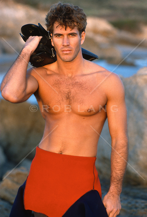 portrait of a sexy man in a wetsuit pulled down to his waist