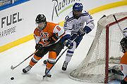 RIT forward Gabe Valenzuela and Air Force defenseman Jonathan Kopacka chase a puck behind the Air Force net during the Atlantic Hockey semifinal at the Blue Cross Arena at the War Memorial in Rochester on Friday, March 18, 2016.