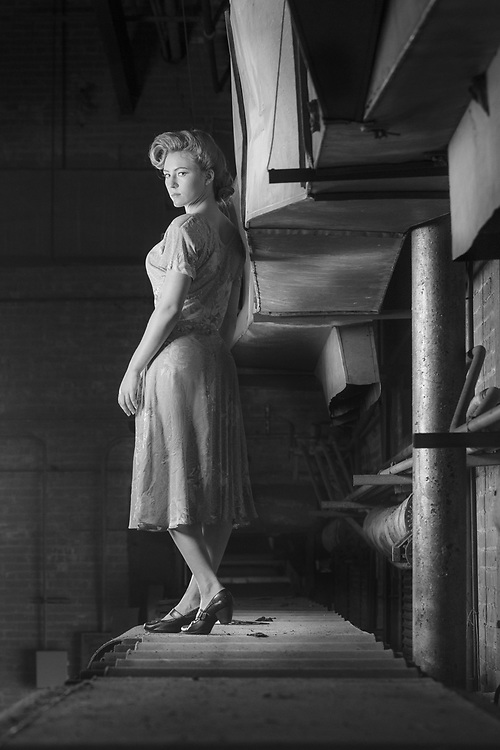 1940s model in vintage dress and hair poses on conveyor belt in abandoned sugar factory