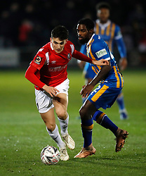 Salford City's Tom Walker (left) and Shrewsbury Town's Anthony Grant battle for the ball during the Emirates FA Cup, first round replay match at the Peninsula Stadium, Salford.