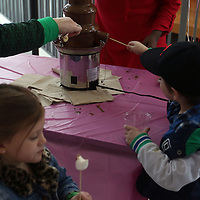 Libby Ezell | BUY at PHOTOS.DJOURNAL.COM<br /> Kently Hardin, 4, sticks his marshmellows under one of the many chocolate fountains at Saturday's NEWMS Chocolate Festival