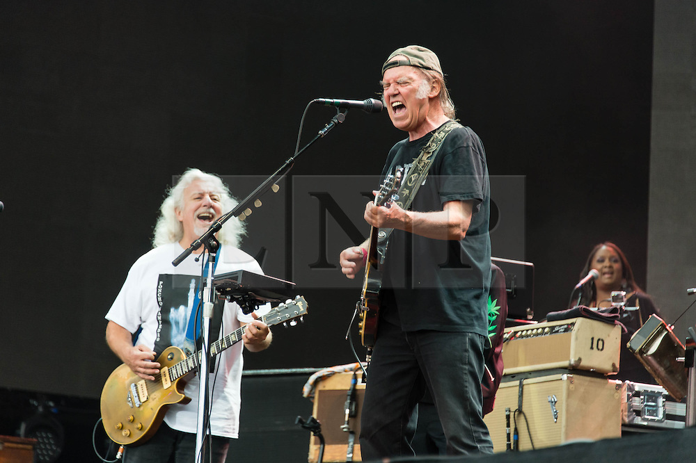 """© Licensed to London News Pictures. 12/07/2014. London, UK.   Neil Young and Crazy Horse performing live at Hyde Park as part of the British Summer Time series of outdoor concerts.In this picture - Neil Young (centre), Frank Sampredo (left).   Crazy Horse is a rock band long associated with Neil Young,  consisting of members Rick Roses, (bass, vocals), Ralph Molina (drums, vocals), Frank """"Poncho"""" Sampedro ( guitar, organ, keyboards).  Photo credit : Richard Isaac/LNP"""