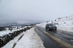 © Licensed to London News Pictures.04/03/16. Ilkley, UK.  A car makes it's way up to the snow covered hills in Ilkley after heavy snowfall over night in Yorkshire caused chaos on many roads. Forecasters are predicting more cold weather this week as Storm Jake takes hold. Photo credit : Ian Hinchliffe/LNP