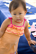 Asian toddler working at childrens craft table. Dragon Festival Lake Phalen Park St Paul Minnesota USA