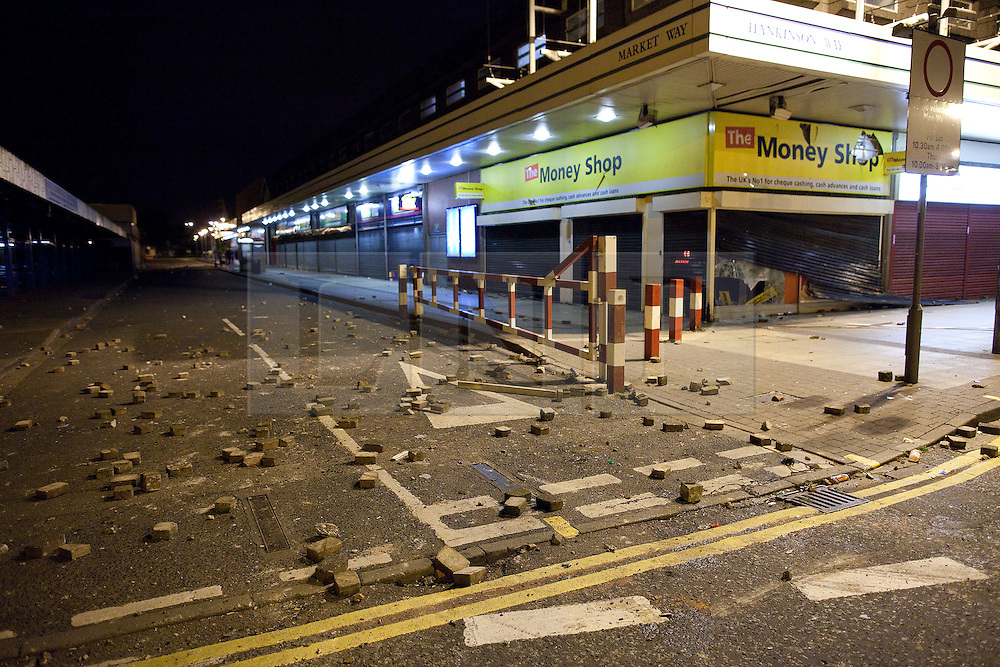 © Licensed to London News Pictures. 10/08/2011. Salford, UK. The streets are strewn with bricks and shops are smashed. Scenes of desctruction around Salford Precinct in Greater Manchester, where people rioted and looted. Photo credit : Joel Goodman/LNP