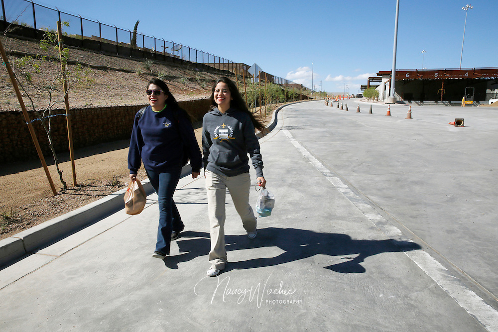 "Kino Teens Marian Enriquez and Nicole Davison carry donated goods as they walk toward Mexico at the Mariposa border crossing in Nogales, Ariz. They were on their way to serve dinner at the ""comedor,"" the kitchen and dinning hall of the the Aid Center for Deported Migrants, in Nogales, Sonora, in this 2014 file photo. Pope Francis wrote a personal letter to the Kino Border Initiative's executive director praising and encouraging the teens in their work for migrants. (Photo taken April 2, 2014) (Photo by Nancy Wiechec)"