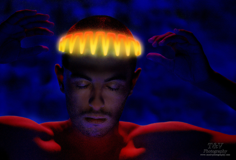 Young man with glowing headpiece and arms raised against a blue background.Black light