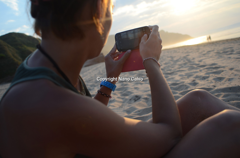 Young woman takes a photo of the beach at sunset, with her mobile phone