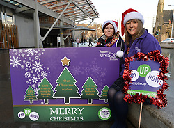 Pictured: Laura McDonald and Lillian Macer from UNISON with a giant Christmas card and cracker demanding fair pay for NHS workers.<br /> <br /> UNISON delivers 5000 'Fair Pay Now' cards to MSP's at the Scottish Parliament, demanding the Scottish Government 'pays up on NHS pay'.<br /> <br /> &copy; Dave Johnston/ EEm