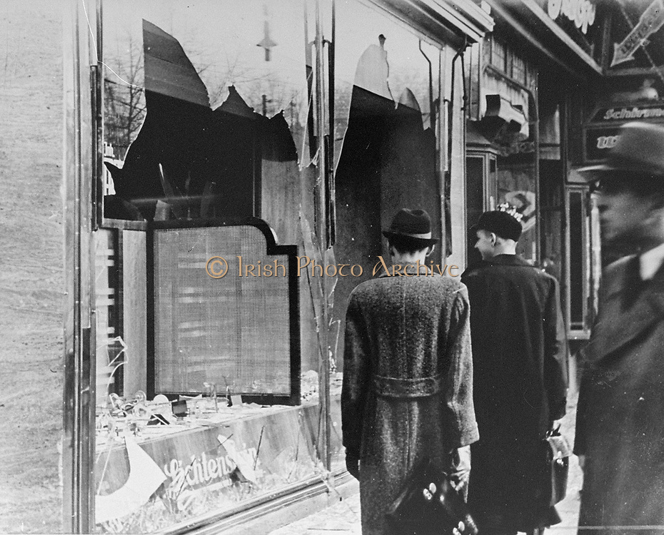 Germans pass by the smashed windows of a Jewish-owned shop. The aftermath of Kristallnacht (Night of Broken Glass) 9-10 November 1938, the German anti-semitic pogrom , when over 200 Synagogues were destroyed and thousands of Jewish homes and businesses  were ransacked.