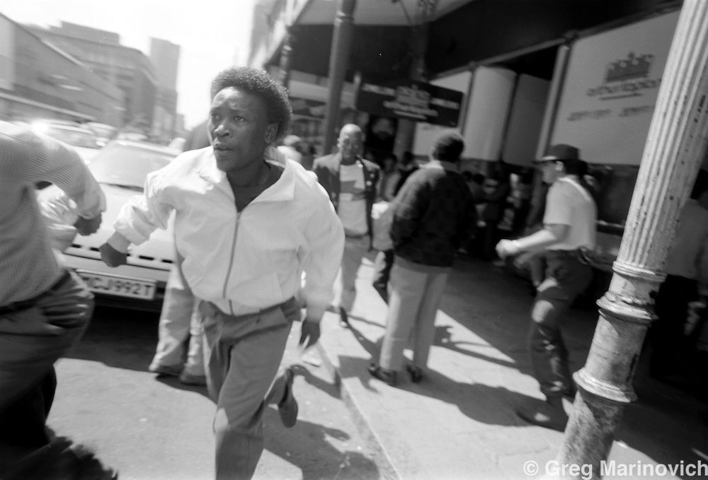 SOUTH AFRICA Sept 23, 1989: Black counter-protesters flee from confrontations at a Right-wing Afrikaner gathering at Church Square in downtown Pretoria, northern Transvaal (now Limpopo Province)  (Photo by Greg Marinovich)