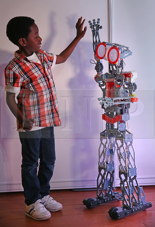 © Licensed to London News Pictures. 04/11/2015. London, UK. Six year old Babafewa high fives a Meccano Meccanoid robot at the Dream Toys Christmas event. Photo credit: Peter Macdiarmid/LNP