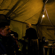A babushka prepares food at a self-defence group's tent near the Crimean border, in the Kherson region of Ukraine.
